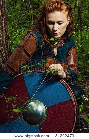 Serious redhead scandinavian woman posing with shield in a forest