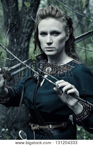 Redhead scandinavian woman with sword in a forest