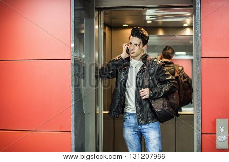 Handsome young man leaning against mirror inside an elevator or lift, calling someone on cell phone