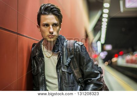 Handsome young male traveler in train station with backpack, looking to a side