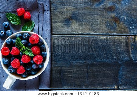 Old wooden table with assortment berries blueberries and raspberries at textile napkin over dark textured background. Top view composing with space for text. Flat lay. Rustic style.