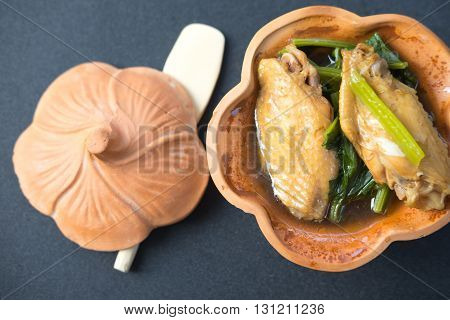 Chinese vegetable stew mixture of vegetables and chicken legs on pottery bowl