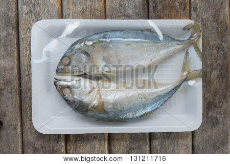 Two of steamed mackerel fish in foam tray on wood