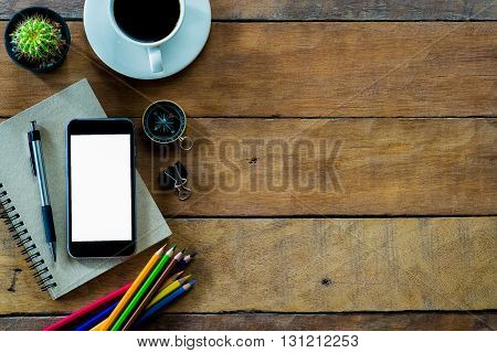 Office stuff with blank screen smartphone coffee cup penpencil and notebook.Top view with copy space