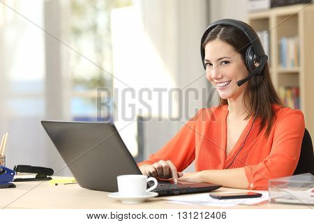 Beautiful freelancer female posing and working on line with headset with mic and looking at camera in a little office desktop or home