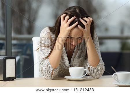 Sad and depressed woman alone in a lonely bar after a break up with a rainy winter day outdoor in the background