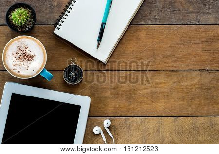 Office stuff with blank screen tablet coffee cup pencil and leather notebook.Top view with copy space