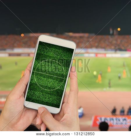 Hand holding mobile smart phone with football stadium blur image of a football field as background.