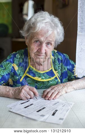 An elderly woman fills out forms for payment of utility services.