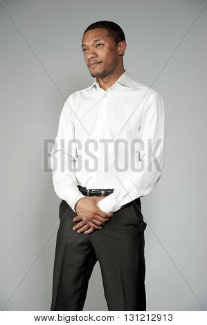 An attractive African American boy wearing a white button down and black slacks on a gray background in a studio setting.