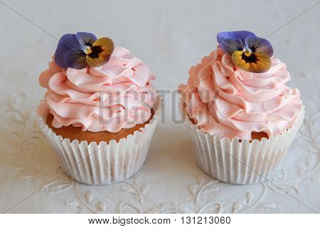Homemade pink frosting vanilla cupcakes with edible flowers