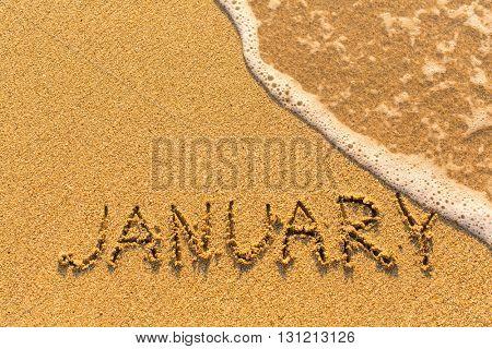 January - written by hand on a golden beach sand.
