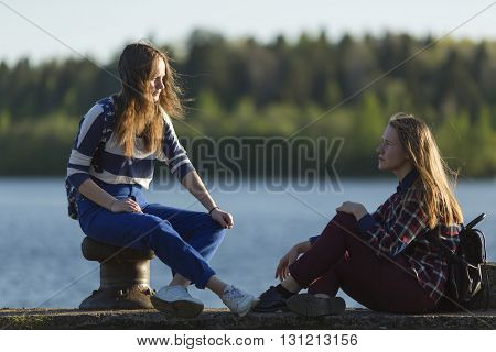Teen girls sitting on a pier near the water in the sun.