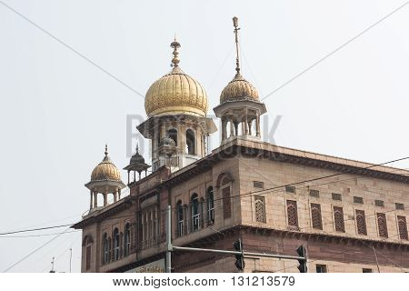 An old gurdwara with ancient architecture named as Sis Ganj, which is a praying temple for the Sikhs. The dome of the gurdwara is golden and the name is written on a plaque.