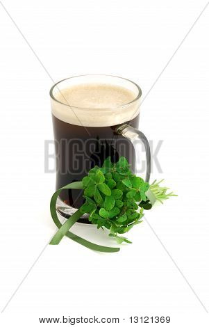 Dark Beer In Glass And Bouquet Of False Shamrock With Green Ribbon