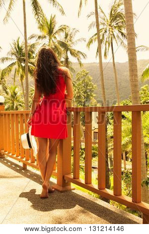 Young beautiful girl standing on the balcony at a resort in the background of the rainforest