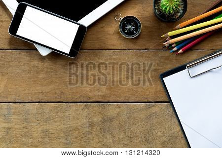 Office workspace with blank screen tablet blank screen smartphone blank screen note paper over blackboard and color pencil .Top view with copy space