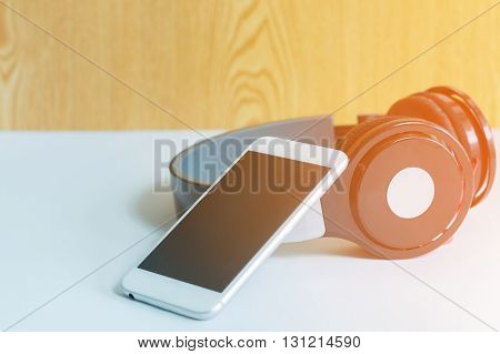 music concept - smartphone and headphones on the wood background, smartphone and headphones close-up