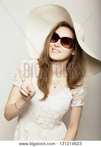 beautiful girl in broad-brimmed hat and sunglasses posing and expresses different emotions.
