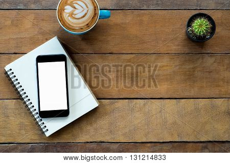 Office stuff with blank screen smartphone notebook and coffee cup .Top view with copy space