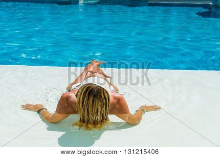 Beautiful woman relaxing in a pool at summer resort
