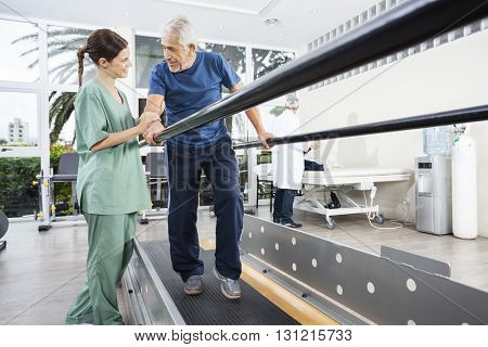 Physiotherapist Looking At Senior Patient Walking Between Parall