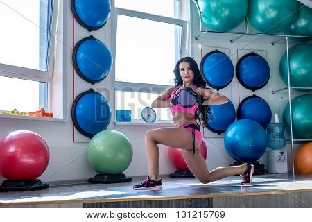 Image of pretty woman posing while exercising in gym