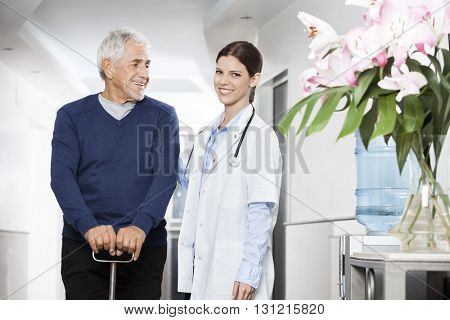 Confident Female Doctor Standing With Senior Man