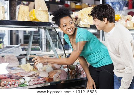 Couple Choosing Product From Display Cabinet
