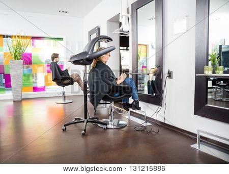Customers Undergoing Hair Treatment In Parlor