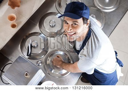 Portrait Of Waiter Leaning On Lids At Counter In Parlor