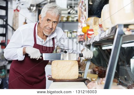 Happy Salesman Slicing Cheese With Knife In Shop