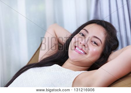 Relaxing woman lie down comfortable and smiling happy looking at camera. Resting young asian female clasping her hands behind her nape of the neck.