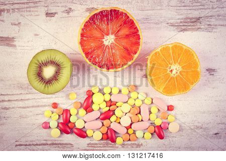 Vintage photo Fresh natural fruits and medical pills tablets and capsules on rustic background choice between healthy nutrition and medical supplements healthy lifestyle