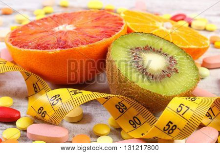 Fresh natural fruits tape measure pills tablets and capsules on rustic background concept of slimming and choice between healthy nutrition and supplements