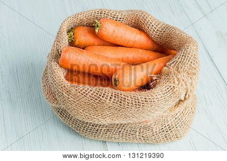 A sack with carrots on a bright wooden background.
