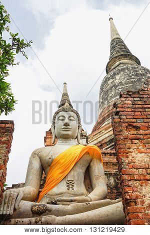 Ancient concrete Buddha sculpture with old pagoda in the back at Ayutthaya Thailand in cloudy blue sky