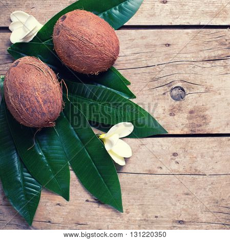Coconuts on leaves on aged wooden background. Selective focus. Flat lay. Top view with copy space. Square image.