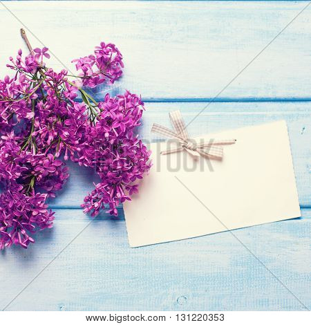 Fresh lilac flowers and empty tag on blue wooden planks. Selective focus. Place for text. Flat lay. Square image.