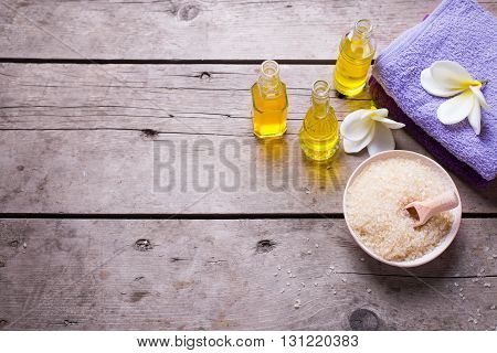Spa or wellness setting in yellow and violet colors. Bottles wih essential aroma oil towels sea salt on aged wooden background. Selective focus. Place for text. Top view.