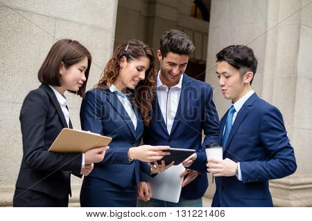 Group of business people discuss on digital tablet