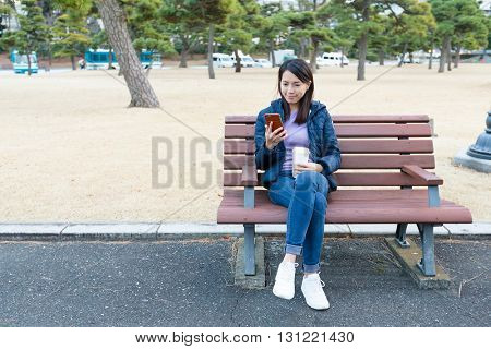 Woman use of cellphone at outdoor park