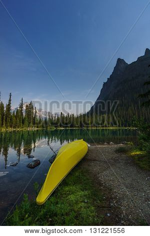 Yellow canoe resting ashore Lake O'Hara in British Columbia, Canada