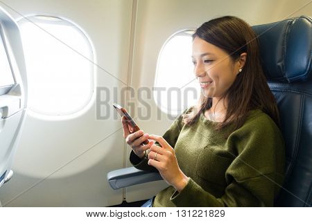 Woman use of mobile phone inside airplane