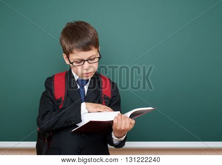 school boy portrait in black suit on green chalkboard background with red backpack read book, education concept
