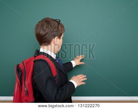 school boy portrait in black suit on green chalkboard background with red backpack, education concept