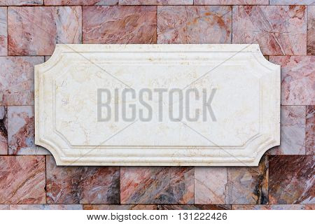 A signboard marble on brown marble wall.