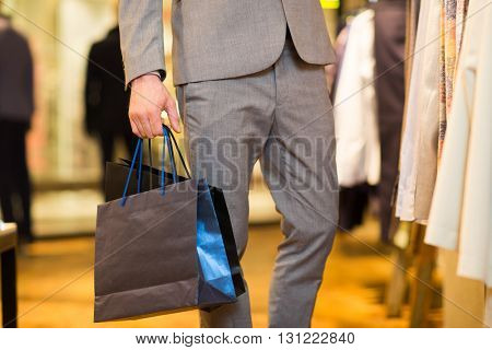 sale, fashion, retail, business style and people concept - close up of man in suit with shopping bags at clothing store