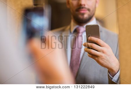 sale, shopping, fashion, style and people concept - close up of young man in suit with smartphone taking mirror selfie at clothing store