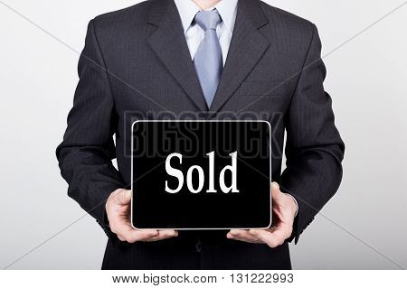technology, internet and networking in business concept - businessman holding a tablet pc with sold sign. Internet technologies in business.